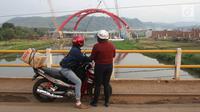 Warga menonton kendaraan pemudik yang melintasi Jembatan Kali Kuto pada ruas tol fungsional Batang - Semarang, Gringsing, Jateng, Rabu (13/6). Berfungsinya Jembatan ini akan memperlancar arus mudik dan arus balik Lebaran 2018. (Liputan6.com/Arya Manggala)