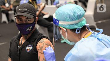 Petugas menyuntikkan vaksin COVID-19 kepada atlet di Istora Senayan, Jakarta, Jumat (26/2/2021). Pemerintah memulai vaksinasi COVID-19 tahap pertama untuk para atlet. (Liputan6.com/Faizal Fanani)