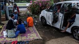 Sejumlah pemudik menggelar tikar beristirahat di rest area Tol Timur - Palimanan - Kanci,  Cirebon, Jawa Barat, Sabtu (1/7). Mereka memanfaatkan rest area untuk beristirahat sebelum meneneruskan perjalanan kembali ke Jakarta. (Liputan6.com/Faizal Fanani)