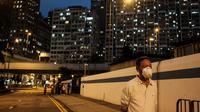 Seorang pria memakai masker berjalan di sepanjang jalan di Hong Kong (21/4/2020). Kepala eksekutif Carrie Lam mengatakan langkah-langkah jarak sosial dan beberapa pembatasan bisnis akan berlanjut selama dua minggu hingga setidaknya 7 Mei. (AFP/Anthony Wallace)