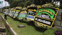 Warga mengambil gambar karangan bunga ucapan duka cita untuk Probosutedjo yang memenuhi Jalan Diponegoro, Jakarta, Senin (26/3). Probosutedjo meninggal dunia pada usia 87 tahun. (Liputan6.com/Arya Manggala)