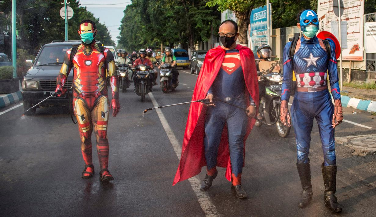 Petugas kepolisian yang berpakaian superhero menyemprotkan cairan disinfektan di jalan kawasan Pasuruan, Jawa Timur, Kamis (9/4/2020). Penyemprotan cairan disinfektan tersebut bertujuan untuk mengantisipasi penyebaran Virus Corona (COVID-19). (JUNI KRISWANTO / AFP)