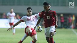 Gelandang Indonesia U-23, Febri Hariyadi (kanan) berebut bola dengan pemain Bahrain pada laga PSSI Anniversary 2018 di Stadion Pakansari, Kab Bogor, Jumat (27/4). Babak pertama Indonesia tertinggal 0-1. (Liputan6.com/Helmi Fithriansyah)