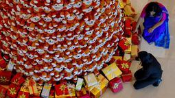 Staff menyusun bingkisan kado di bawah pohon Natal dari boneka beruang teddy di lobi sebuah hotel di Bangalore, India, Rabu (28/11). Ratusan boneka beruang disusun sedemikian rupa hingga membentuk pohon natal cantik. (MANJUNATH KIRAN / AFP)