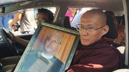 Seorang biksu Buddha memegang potret Ko Ni saat pemakaman Ko Ni di Yangon, Myanmar (30/1). Ko Ni adalah salah seorang figur Muslim ternama di negara yang mayoritasnya beragama Buddha itu. (AP Photo/Esther Htusan)