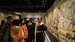 Pemandu menjelaskan lukisan thangka bertema panda kepada pengunjung di Perpustakaan Provinsi Sichuan, Chengdu, Provinsi Sichuan, China, 11 Oktober 2020. Thangka adalah semacam lukisan di atas sutra bersulam dan biasanya menggambarkan makhluk suci Buddhis, peristiwa, atau mandala. (Xinhua/Wang Xi)
