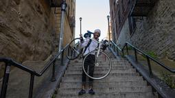 Elliott Raylassi, seorang penduduk lokal sejak tahun 2001, membawa sepedanya menaiki tangga di kawasan Bronx, New York, 23 Oktober 2019. Wisatawan memadati tangga panjang itu untuk berpose ala Joker atau sekadar mengunggahnya di Instagram. (Don Emmert / AFP)