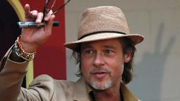 """Brad Pitt menyapa penggemar saat menghadiri acara karpet merah untuk film """"Once Upon a Time In Hollywood"""" di Mexico City (12/8/2019). Aktor 55 tahun itu tampil necis dalam setelan jas krem, sepatu boot, dan kemeja mustard. (AP Photo/Marco Ugarte)"""