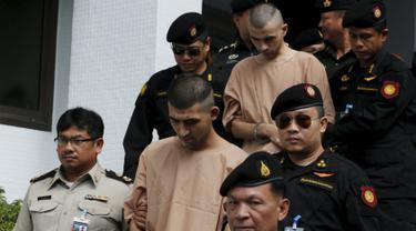 Dua tersangka pemboman Yusufu Mieraili dan Bilal Mohammed berjalan dikawal petugas saat meninggalkan Pengadilan militer (24/11). Pengadilan Thailand telah mendakwa dua orang yang dituduh melakukan serangan bom di Bangkok. (REUTERS /Chaiwat Subprasom)
