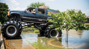 Truk monster menerobos genangan air saat membantu warga yang menjadi korban Badai Harley di Port Arthur, Texas, AS (1/9). Truk raksasa ini menjadi salah satu kendaraan yang diandalkan usai Badai Harley menghantam Texas. (AFP Photo/Emily Kask)
