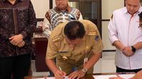 Gubernur Olly Dondokambey menandatangani kesepakatan dengan stakeholder terkait Pilkada 2020. (Liputan6.com/Yoseph Okanubun)