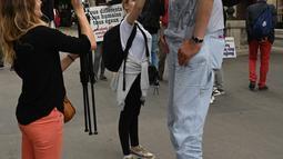 Wartawan saat mewawancarai Brahim Takioullah yang memiliki tinggi tubuh 2 meter 46 centimeter saat berkumpul dengan orang-orang tertinggi dunia di Champs-Elysees Avenue di Paris, Prancis (14/6/2019). (AFP Photo/Dominique Faget)