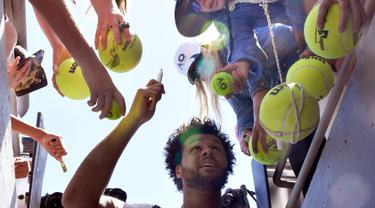 Petenis asal Prancis, Jo-Wilfried Tsonga usai membubuhkan tanda tangan di bola tenis penggemarnya setelah memenangkan pertandingan putaran kedua Australia Terbuka melawan petenis Serbia Dusan Lajovic di Melbourne, Rabu (18/1). (AP Photo/Andy Brownbill)