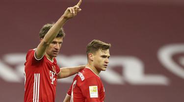 Pemain Bayern Munchen Joshua Kimmich (kanan) merayakan bersama Thomas Mueller usai mencetak gol ke gawang Bayer Leverkusen pada pertandingan Bundesliga di Stadion Allianz Arena, Munchen, Jerman, Selasa (20/4/2021). Bayern Munchen menang 2-0. (AP Photo/Matthias Schrader, Pool)