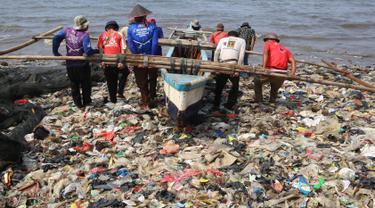 Nelayan beraktivitas di pantai Sukaraja yang tercemar sampah plastik di Bandar Lampung pada 8 September 2019. Selain berserakan dan aroma tak sedap, sampah-sampah di pesisir tersebut juga menyebabkan banyaknya ikan yang mati. (Photo by PERDIANSYAH / AFP)