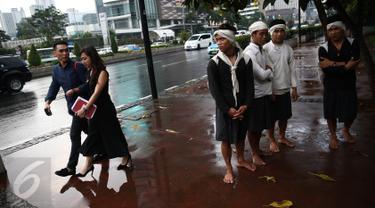 Empat warga Baduy berteduh ketika hujan mengguyur kawasan Bundaran HI, Jakarta, Selasa (6/9). Warga Baduy berjalan ratusan kilometer dari kampung mereka tanpa alas kaki dan sama sekali tidak menggunakan kendaraan bermotor. (Liputan6.com/Faizal Fanani)