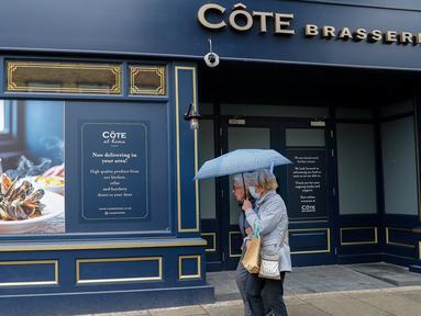 Orang-orang berjalan melewati sebuah restoran yang tutup sementara di London, Inggris, pada 13 Oktober 2020. Tingkat pengangguran Inggris melonjak ke level tertinggi dalam tiga tahun terakhir di angka 4,5 persen untuk periode Juni-Agustus 2020. (Xinhua/Han Yan)