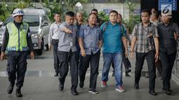 Anggota DPRD Provinsi Jambi Supriyono (depan), PLT Dinas PUPR Jambi Arfan (belakang) dikawal petugas memasuki Gedung KPK, Jakarta, Rabu (29/11). OTT tersebut terkait kasus dugaan suap APBD Jambi tahun 2018. (Liputan6.com/Faizal Fanani)