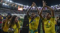 Bek Brasil, Dani Alves, bersama putranya merayakan gelar juara Copa America 2019 setelah mengalahkan Peru pada laga final di Stadion Maracana, Rio de Janeiro, Minggu (7/7). Brasil menang 3-1 atas Peru. (AFP/Carl De Souza)