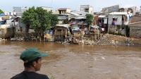 Warga berada di seberang pemukiman padat di bantaran kali Ciliwung, Jakarta, Kamis (16/4/2020).  Menko Bidang Perekonomian Airlangga Hartarto mengungkap proyeksi pemerintah terhadap angka kemiskinan naik dari 9,15 persen menjadi 9,59 persen akibat pandemi COVID-19. (Liputan6.com/Helmi Fithriansyah)