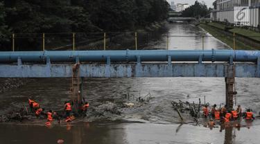 Pasukan oranye membersihkan sampah yang tersangkut di aliran sungai Ciliwung di kawasan Sudirman, Jakarta, Jumat (9/2). Meningkatnya debit air di Bendungan Katulampa, aliran air yang masuk ke Sungai Ciliwung membawa sampah. (Liputan6.com/Faizal Fanani)