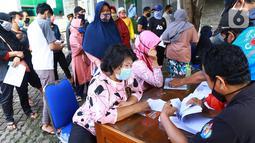 Warga antre menerima Bantuan Sosial Tunai (BST) di Kelurahan Pondok Benda, Kecamatan Pamulang, Tangerang Selatan, Minggu (10/01/2021). Sebanyak 92.737 kepala keluarga tercatat sebagai penerima BST di wilayah Tangerang Selatan senilai Rp300 ribu. (Liputan6.com/Fery Pradolo)