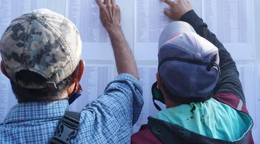 Para warga terdampak perpanjangan PPKM Darurat di Garut, Jawa Barat tengah melihat daftar nama mereka dalam deretan nama yang telah diseleksi Pemda Garut, sebagai penerima bansos tunai Rp 250 ribu per orang.