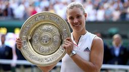 Petenis Jerman, Angelique Kerber tersenyum saat berpose dengan trofi usai mengalahkan petenis AS, Serena Williams pada final tunggal putri kejuaraan Tenis Wimbledon 2018 di London, (14/7). Kerber menang atas Williams 6-3,6-3. (AP Photo/Jonathan Brady)