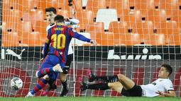 Striker Barcelona, Lionel Messi, mencetak gol ke gawang Valencia pada laga Liga Spanyol di Stadion Mestalla, Minggu (2/5/2021). Barcelona menang dengan skor 2-3. (AFP/Jose Jordan)