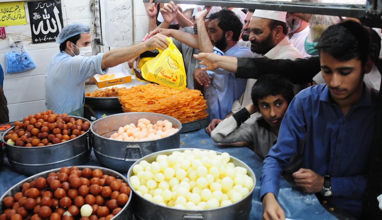 Orang-orang membeli penganan manis tradisional di hari raya Idul Fitri di Peshawar, Pakistan barat laut, pada 25 Mei 2020. Warga Pakistan memiliki tradisi memakan penganan manis saat merayakan Idul Fitri, yang menandai akhir bulan puasa Ramadan. (Xinhua/Saeed Ahmad)
