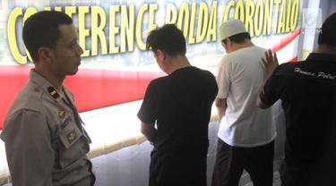 Dua tersangka narkoba dihadirkan saat konferensi pers di Polda Gorontalo, Senin (13/5/2019). Direktorat Reserse Narkoba Polda Gorontalo menetapkan lelaki berinisial WR sebagai tersangka narkoba setelah diringkus saat jelang bulan Ramadhan lalu. (Liputan6.com/Arfandi ibrahim)