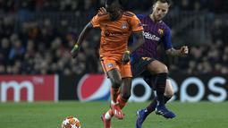 Aksi Bertrand Traore berduel dengan Ivan Rakitic pada leg kedua, babak 16 besar Liga Champions yang berlangsung di Stadion Camp Nou, Barcelona, Kamis (14/3). Barcelona menang 5-1 atas Lyon. (AFP/Lluis Gene)
