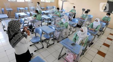 Guru melakukan kegiatan belajar tatap muka dengan penerapan protokol kesehatan COVID-19 di SMAN 2 Cibinong, Kabupaten Bogor, Jawa Barat, Rabu (17/3/2021). Sebanyak 170 sekolah di Kabupaten Bogor mulai menggelar uji coba pembelajaran secara tatap muka hingga 10 April 2021. (merdeka.com/Arie Basuki)