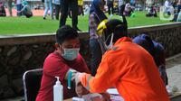 Petugas mengambil sampel darah saat melakukan rapid test pendeteksian COVID-19 kepada tenaga medis di Stadion Patriot Candrabhaga, Bekasi, Rabu (25/3/2020). Pemeriksaan hanya diperuntukan bagi tenaga medis seluruh puskesmas, dan rumah sakit yang ada di Kota Bekasi. (Liputan6.com/Herman Zakharia)