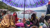 Anggota keluarga penumpang menunggu proses pencarian yang dilakukan tim SAR terhadap korban tenggelamnya KM Sinar Bangun di pelabuhan feri Danau Toba, Sumatera Utara, Rabu (20/6). Kapal tersebut membawa ratusan penumpang. (AFP PHOTO/IVAN DAMANIK)