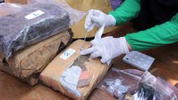 Petugas BNN memperlihatkan barang bukti berupa ganja di lapangan BNN, Jakarta, Kamis ,(7/5/2015). Sebanyak 15.981,37 gram shabu, 4.336,40 gram ganja, 59,44 gram canna chocolate, 285,62 gram happy cookies. (Liputan6.com/Helmi Afandi)