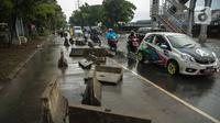 Kendaraan melintas dekat separator busway yang berserakan pascabanjir di Jalan Daan Mogot, Cengkareng, Jakarta, Jumat (3/1/2020). Separator busway tersebut berantakan akibat banjir yang menerjang sejak kemarin. (Liputan6.com/Faizal Fanani)
