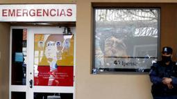Petugas Kepolisian berjaga di depan Rumah Sakit di La Plata, Argentina, Selasa (3/11/2020). Sejumlah fans Argentina berkumpul di depan rumah sakit untuk memberi dukungan kepada sang legenda. (AP/Natacha Pisarenko)
