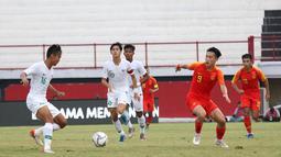 Bek Timnas Indonesia U-19, Komang Teguh  berusaha mengamankan bola dari striker China U-19, Junxian Liu, pada laga ujicoba di Stadion I Wayab Dipta, Bali, Minggu (20/10). Indonesia kalah 1-3 dari China. (Bola.com/Aditya Wany)