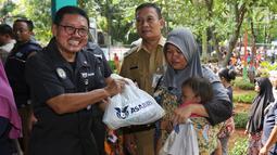 Sekretaris Perusahaan PT Asabri (Persero) Djoko Rachmadhy secara simbolis menyerahkan sembako murah di RPTRA Alur Dahlia, Tegal Alur, Jakarta Barat, Selasa (21/5/2019). PT Asabri (Persero) menjual sebanyak 3 ribu sembako seharga Rp 10 ribu kepada masyarakat sekitar. (Liputan6.com/Johan Tallo)