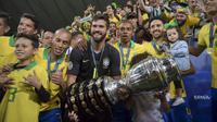 Kiper Brasil, Alisson, bersama rekan-rekannya merayakan gelar juara Copa America 2019 setelah mengalahkan Peru pada laga final di Stadion Maracana, Rio de Janeiro, Minggu (7/7). Brasil menang 3-1 atas Peru. (AFP/Carl De Souza)
