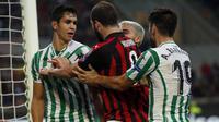 Striker AC Milan, Gonzalo Higuain, bersitegang dengan pemain Real Betis, Aissa Mandi, pada laga Liga Europa di Stadion San Siro, Kamis (25/10/2018). AC Milan takluk 1-2 dari Real Betis. (AP/Antonio Calanni)