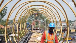 Pekerja menggarap proyek pembangunan Jembatan Penyebaran Orang (JPO) Pasar Minggu di Jakarta Selatan, Kamis (26/9/2019). JPO berdesain artistik senilai Rp 7 miliar tersebut ditargetkan rampung pengerjaannya pada Desember 2019 mendatang. (Liputan6.com/Immanuel Antonius)