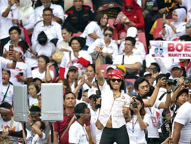 Vokalis grup band SLANK, Kaka tampil membawakan lagu dalam pagelaran Konser Putih Bersatu di Stadion GBK, Senayan, Jakarta, Sabtu (13/4). SLANK membuka penampilan dengan lagu berjudul Mars Slankers, Kuil Cinta dan Lo Harus Gerak. (Fimela.com/Bambang Eros)