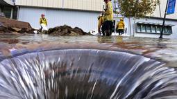Beberapa petugas pemadam kebakaran berusaha mengatasi kerusakan pipa utama saluran air bawah tanah di sekitar Sunset Boulevard di bagian Westwood Los Angeles, (29/7/2014). (REUTERS/Jonathan Alcorn)