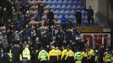 Pendukung Manchester City bereaksi setelah tim kesayangnya dikalahkan Wigan Athletic pada babak kelima Piala FA di Stadion DW, Senin (19/2). Suporter Manchester City melemparkan berbagai benda, termasuk papan iklan, ke arah lapangan. (Oli SCARFF/AFP)