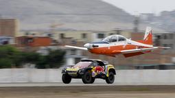Pereli asal Prancis, Sebastien Loeb saat balapan dengan pesawat Angkatan Udara Peru (FAP) di Lima, Peru (6/1). Dengan mengendarai Peugeot 3008, Sebastien Loeb melesat meninggalkan si burung besi tersebut. (AP Photo/Ricardo Mazalan)