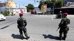 Dua prajurit Marinir TNI Angkatan Laut berjaga di perempatan lampu merah kota Palu pascagempa dan tsunami di Palu, Sulawesi Tengah, Jumat (5/10). Selain berjaga di jalan, mereka juga berjaga di beberapa ruko di Palu. (Liputan6.com/Fery Pradolo)
