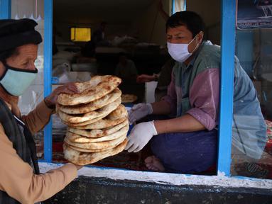 Seorang pria menerima roti gratis dari kota selama lockdownuntuk mencegah penyebaran virus corona, pada bulan puasa suci Ramadan di Kabul, Afghanistan, Senin, (4/5/2020). Muslim di seluruh dunia sedang melaksanakan Ramadan, ketika mereka menahan diri dari makan, minum dari subuh hingga senja. (AP/Ra