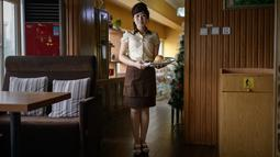 Dalam foto yang diambil pada 28 Juli 2018, seorang karyawan bernama Rim Ok Hyang (20) berpose untuk sesi foto di sebuah restoran hamburger di Pyongyang, Korea Utara. (AFP PHOTO / Ed JONES)